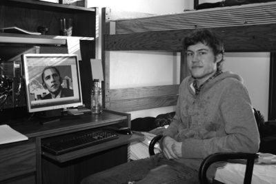 Black and white image of Dirk Miller sitting next to a photo of President Obama on a computer