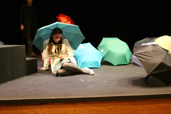 Emily Swora sits under an umbrella on the Umble Center stage, where umbrellas are scattered across the stage
