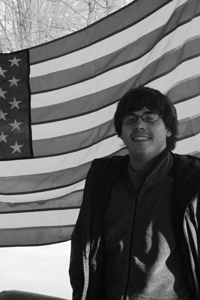Black and white image of Nathan Graber standing in front of an American flag