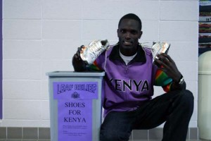 Sam Chege, a senior, shows off his shoes next to the collection bin located in the lobby of the Recreation-Fitness Center. Photo by Brandon Long