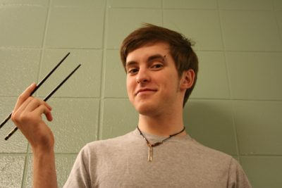 Lucas Nafziger holds chopsticks and poses for a picture