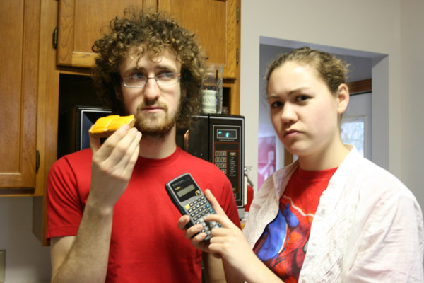 Chase Snyder holds up a pastry as Lydia Short holds up a calculator next to him