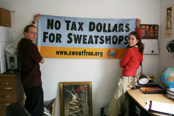 """People hang up a sing that says """"No tax dollars for sweatshops"""""""