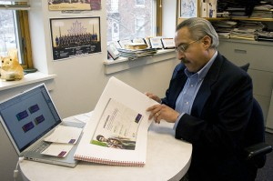 "Richard Aguirre of Goshen College's Public Relations Department leafs through the ""Smart Book"" of promotional materials provided by the Mindpower advertising agency.  Photo by Chase Snyder."
