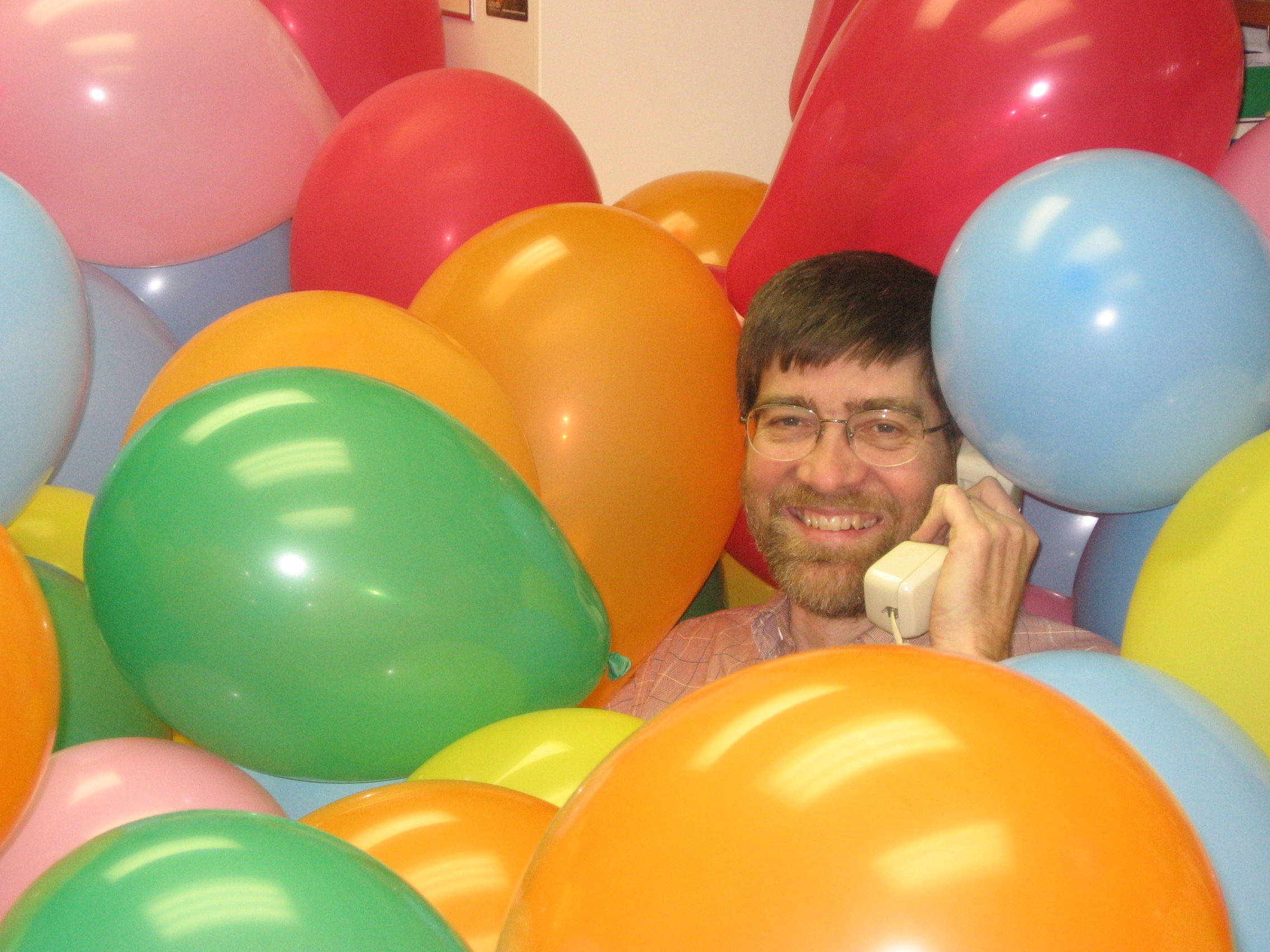 John Ross Buschert found his office flooded with balloons on Tuesday, March 31.  The prank was in response to a quiz question assigned by Buschert.  Photo by Chase Snyder.