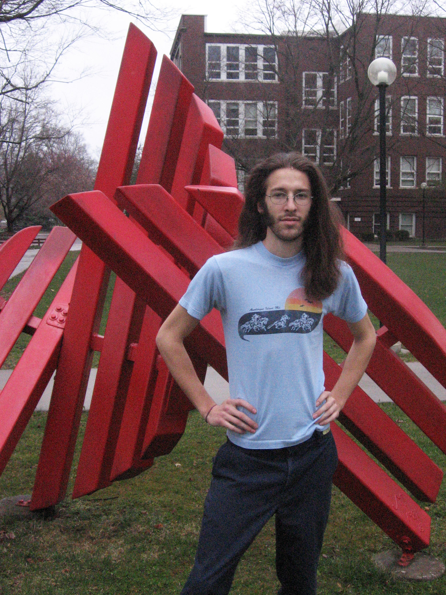 """Jeff Stoesz stands in front of the campus """"Shield"""" sculpture"""