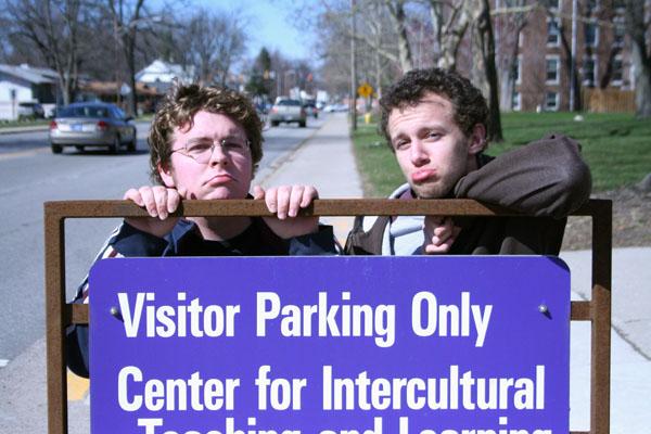 "Michael Martin and David Kempf make sad faces behind a ""Visitor Parking Only"" sign"
