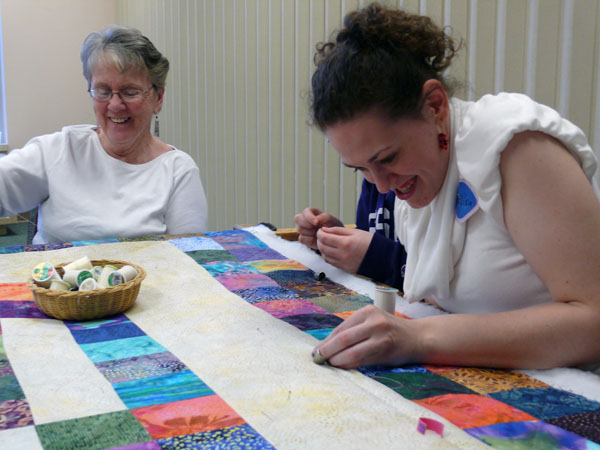 Annalisa Gerig Sickles, a student of Goshen College, participates in a weekly quilting circle with quilters of older generations.  Photo by Paul Boers.