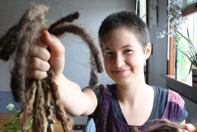 Annali Smucker holds up her dreadlocks after cutting her hair