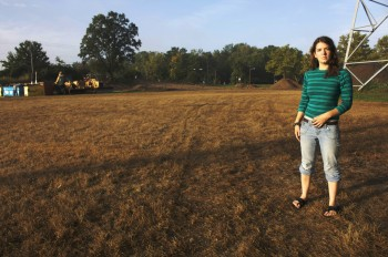 Alana Kenagy stands in front of a plot of land destined to be planted with native grasses. The pile of dirt behind her was excavated to create a water retention pond.  Photo by Angelica Lehman.