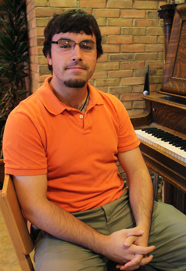 Drew Stoltzfus sits on a piano bench