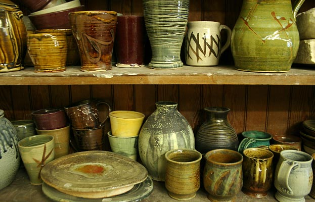 Shelves full of ceramic mugs, pitchers, and plates