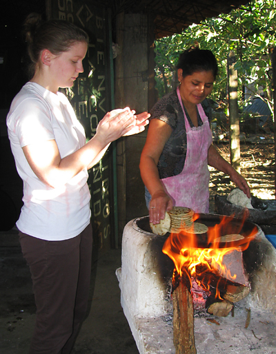 Emily Miller watches as a woman cooks dinner in El Salvador