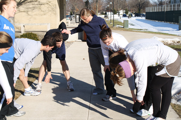 Students rest their elbows on their knees to take a breather after practicing for a half-marathon