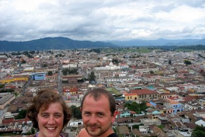 Jodi Beyeler and a man pose for a picture with the city of Quetzaltenango as their backdrop