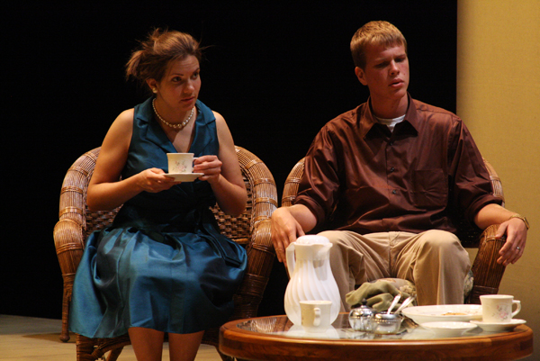 Two student actors in costume sit in armchairs on the Umble Center stage and drink tea