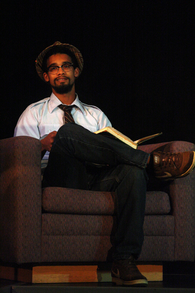 """A participant in the Goshen """"Poetry Cafe"""" sits in an armchair in Newcomer 19"""