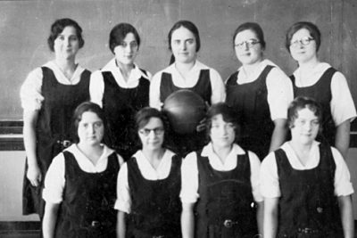 Black and white image from the Mennonite Church USA Archives of a group of nine women in school uniforms standing in front of a chalkboard