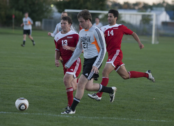 """Jan Dohnal wears a white Goshen jersey and the number """"21"""" as he kicks a soccer ball away from two players in red jerseys"""