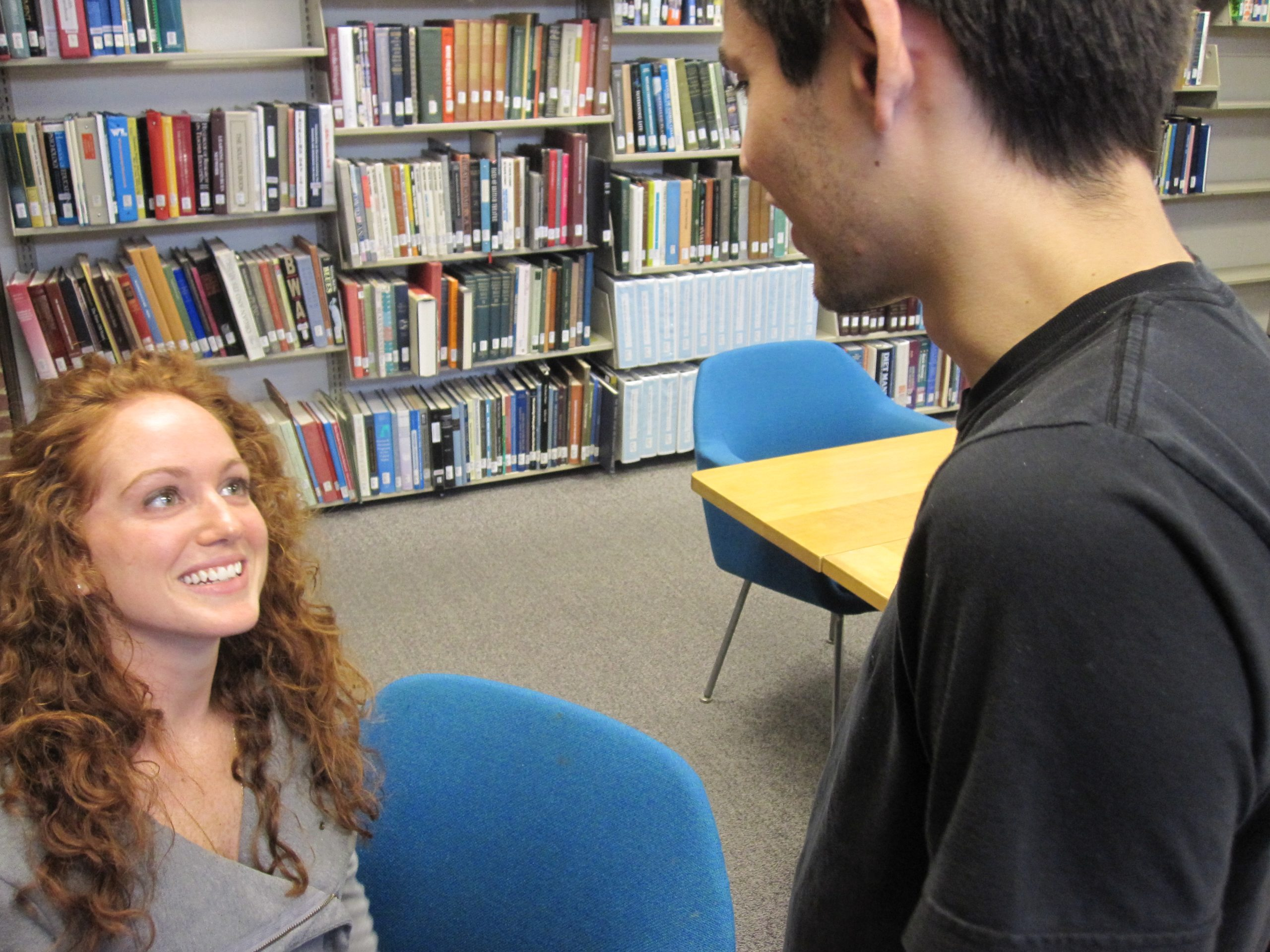 A student talks to a smiling transfer student in the Good Library