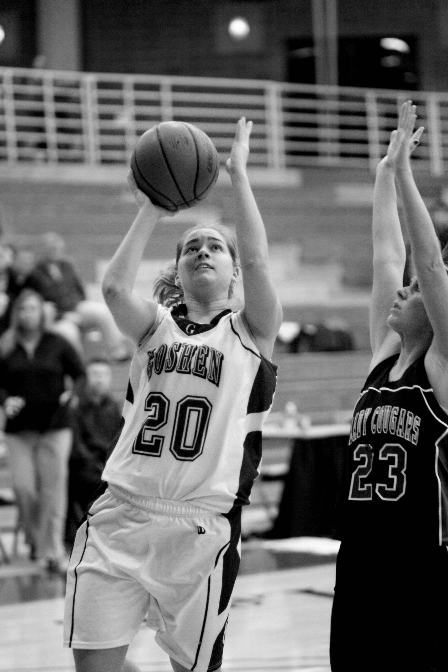 """Black and white image of Jenna Rusmisel handling the ball during a game. She is wearing a number """"20"""" Goshen College jersey"""
