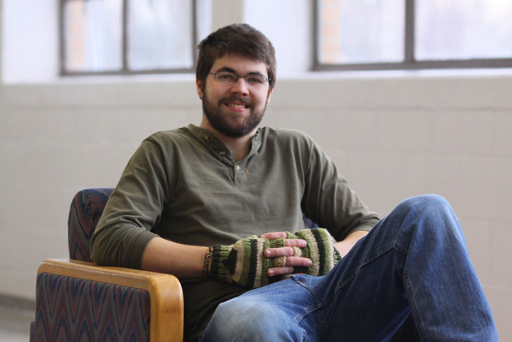 Josh Hertzler sits in a chair and smiles for the camera