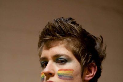 Portrait of Charlotte Barnett. Barnett's face is painted with two rainbow pride flags