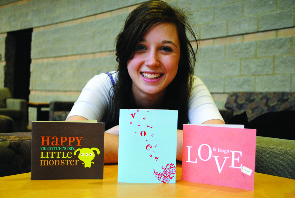 Emma Brooks poses with three of her hand-designed cards