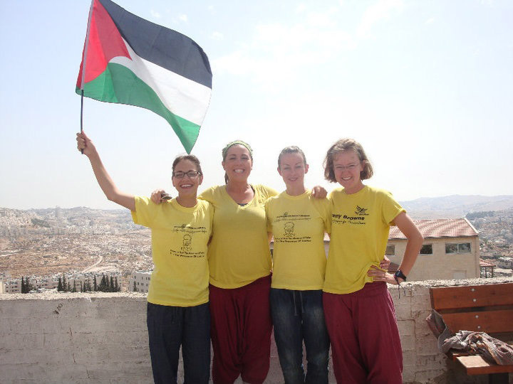 Liz Berg and three other people wave the Palestinian flag