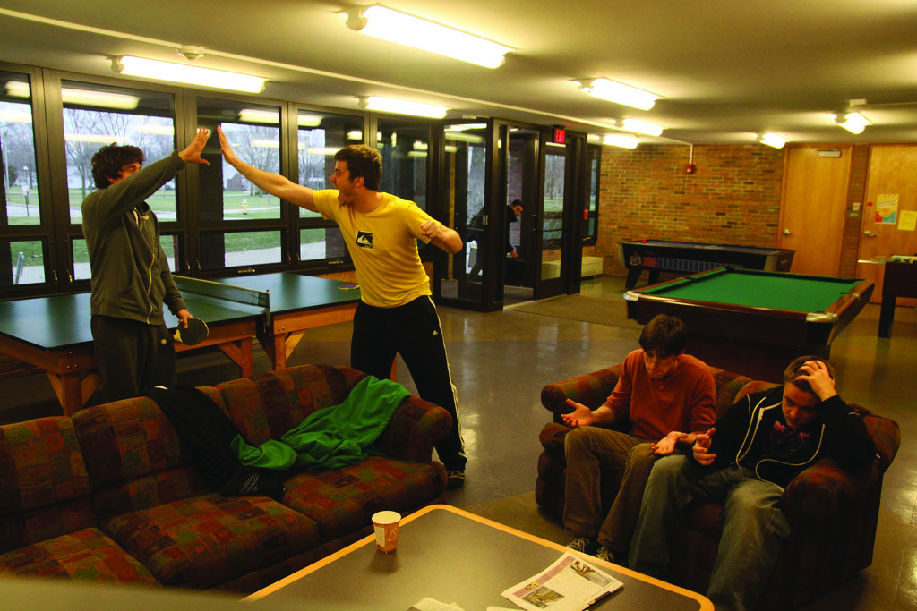 students high five in game room watching march madness