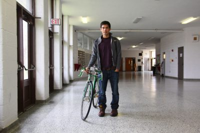 Reuben Maldonado Nafziger walks his bike down a hallway