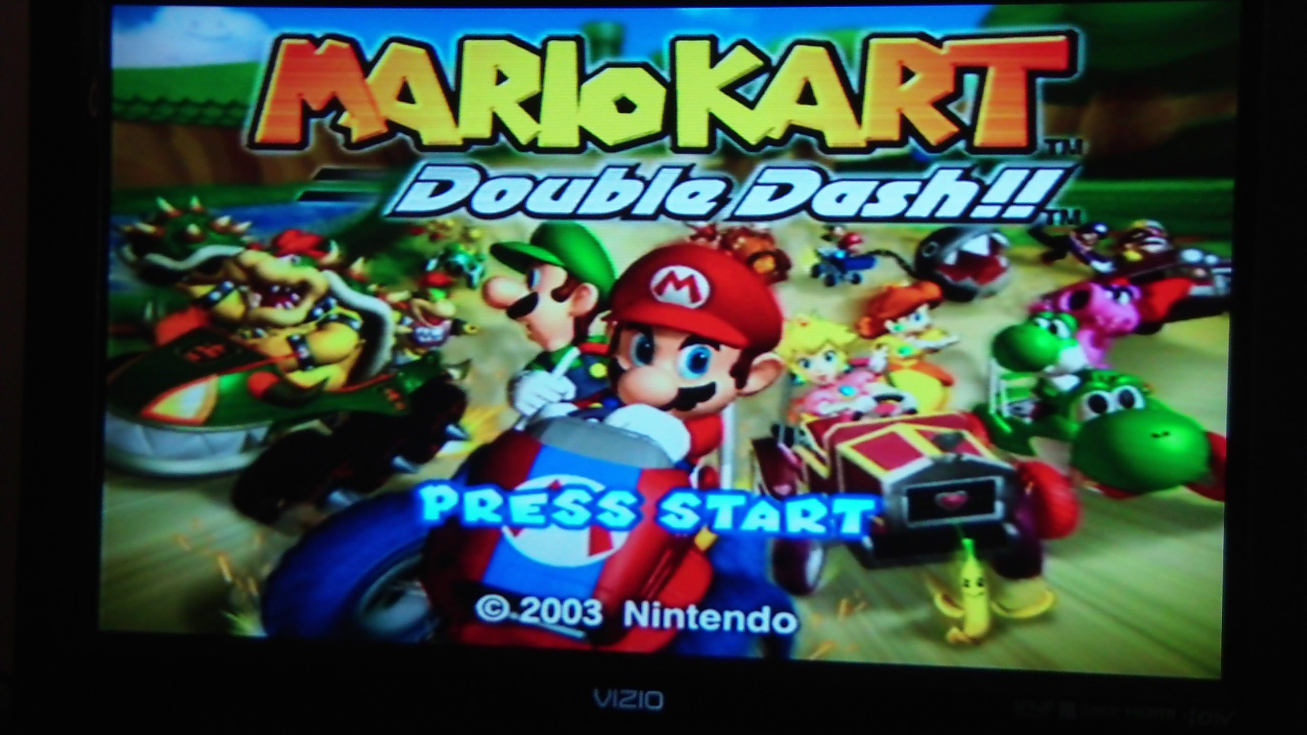"""Photo of a TV screen displaying the video game """"Mario Kart: Double Dash!!"""""""