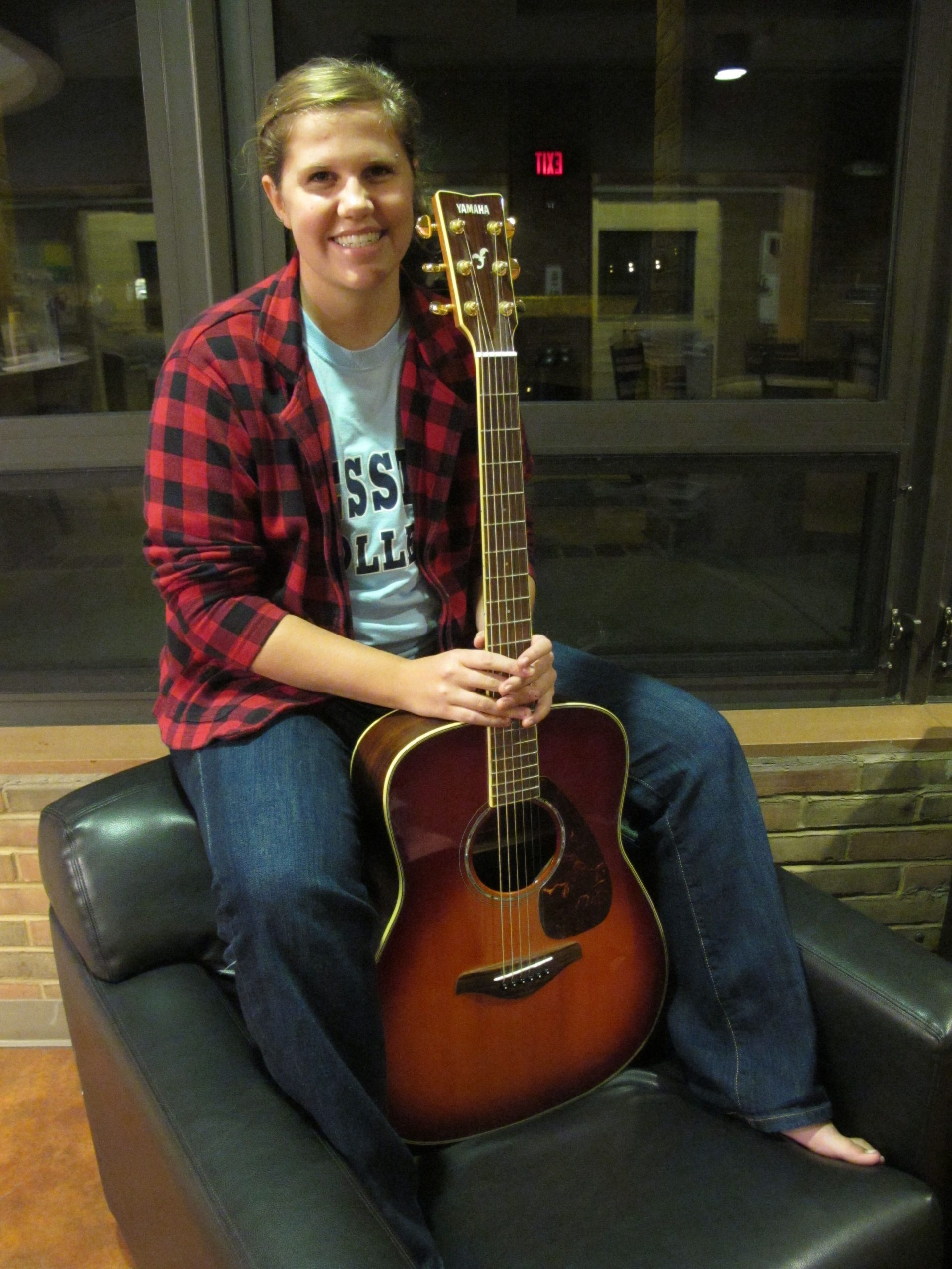 Ana Loucks poses in Java for a picture with her guitar