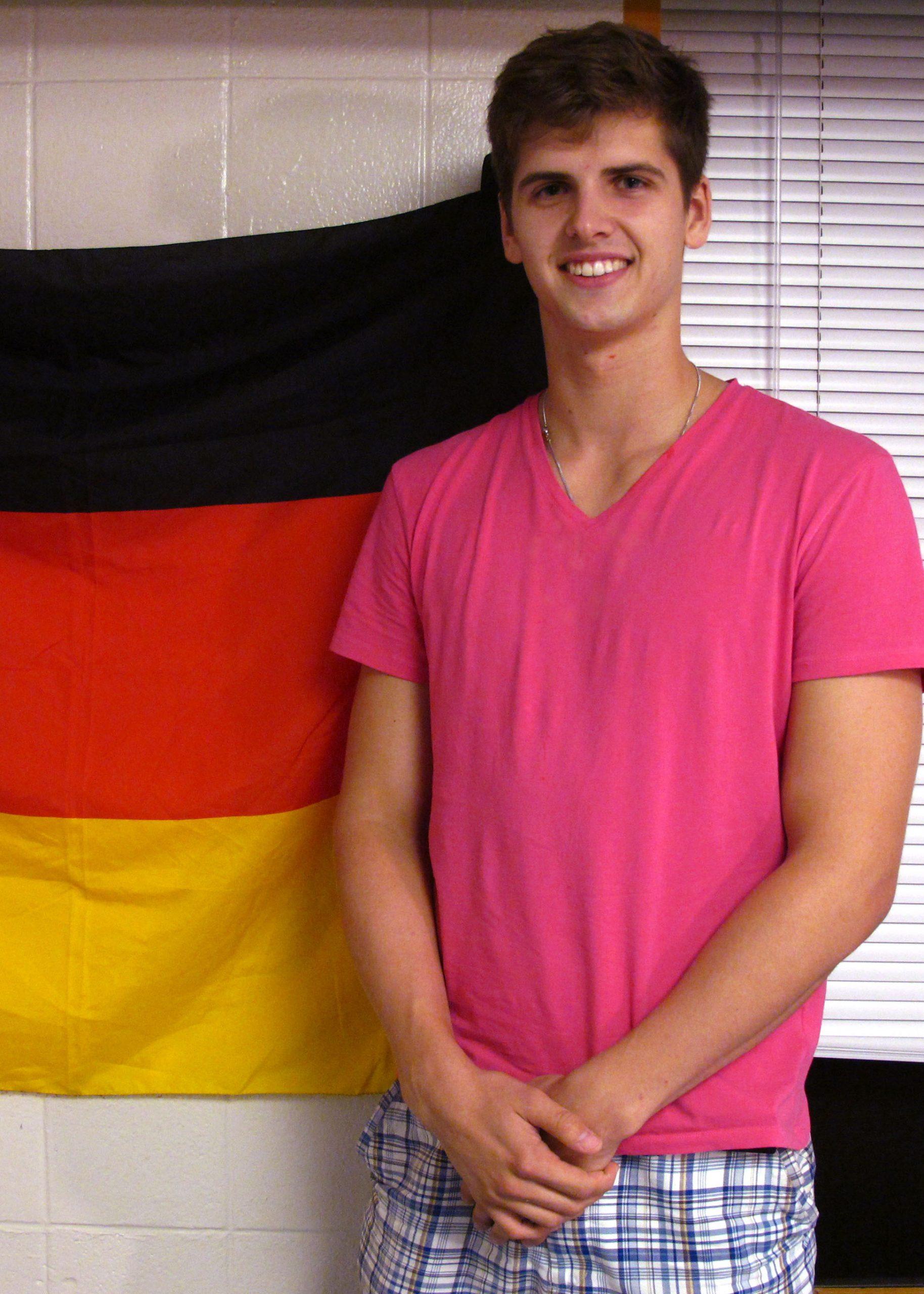 Jan Zawadzki stands next to a German flag in his dorm room