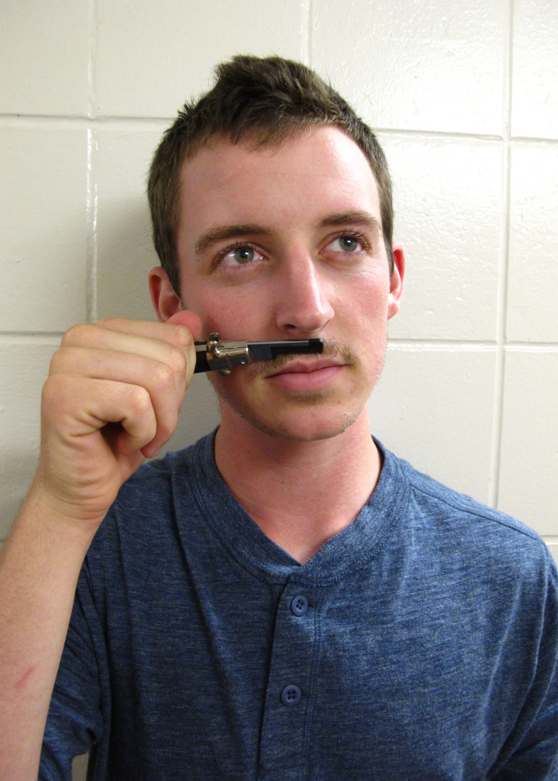 Jonathan Hershberger holds a clipper under his nose in place of a mustache