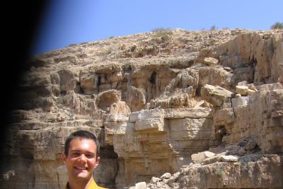 Levi Smucker poses for a picture in front of a Palestinian rockface