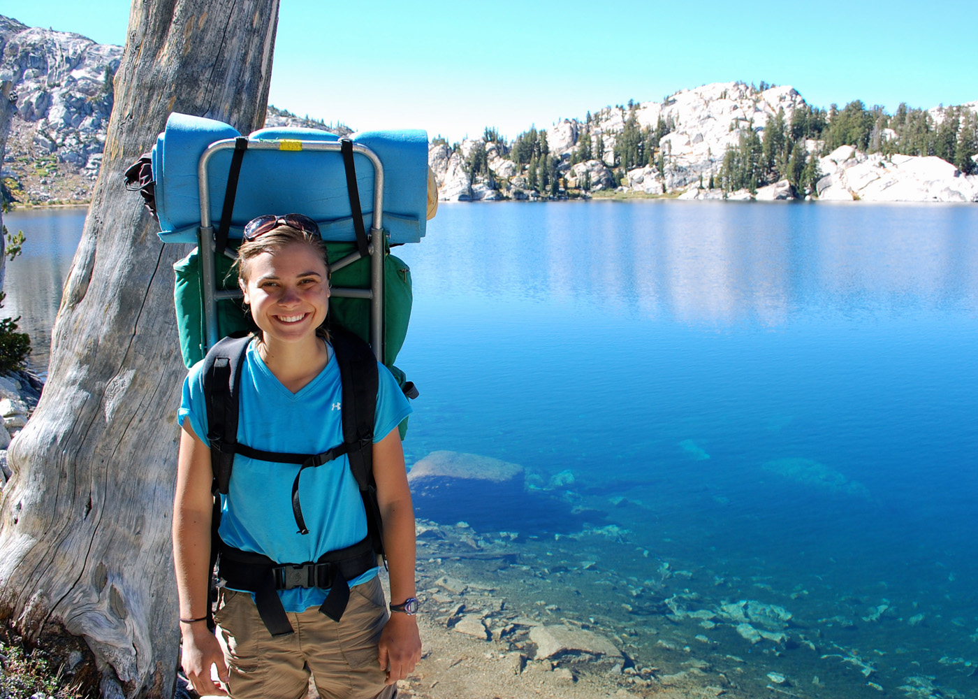 Lydia Alderfer wears a backpacking pack and poses for a picture in front of a lake in Oregon