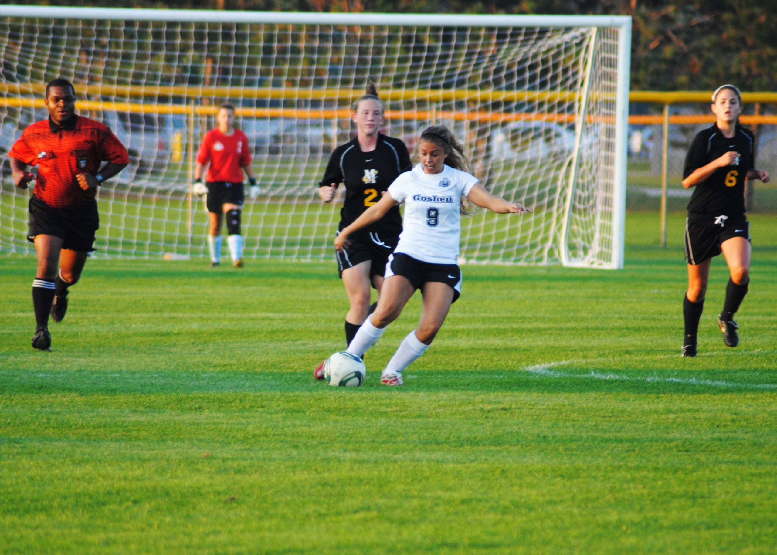 A player on the Goshen women's soccer team dribbles the ball away from opposing players during a game