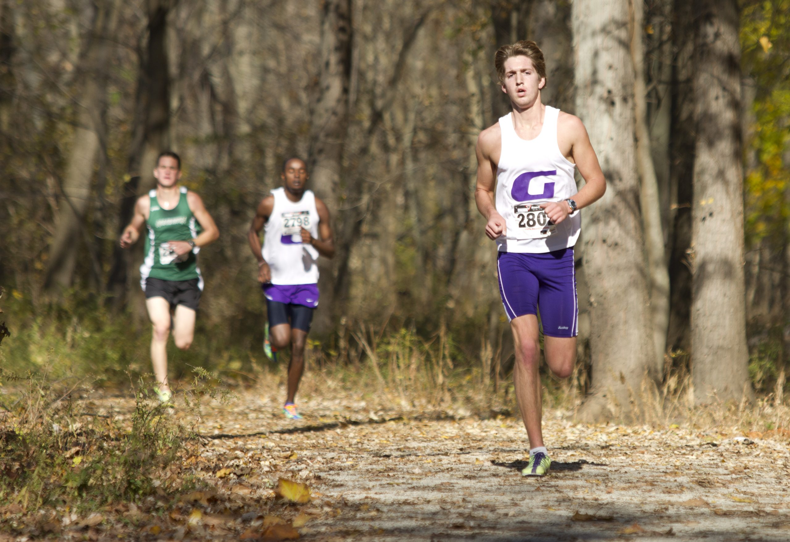Two Goshen College runners race at a cross country meet. A runner from an opposing team races against them through the woods