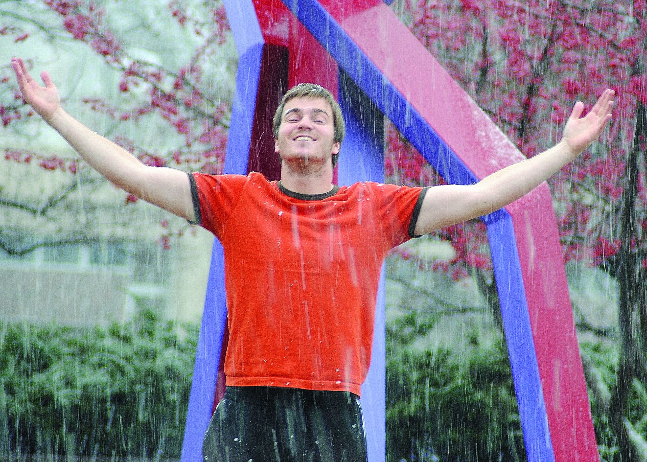 A student enjoys a rainstorm in front of a sculpture on campus