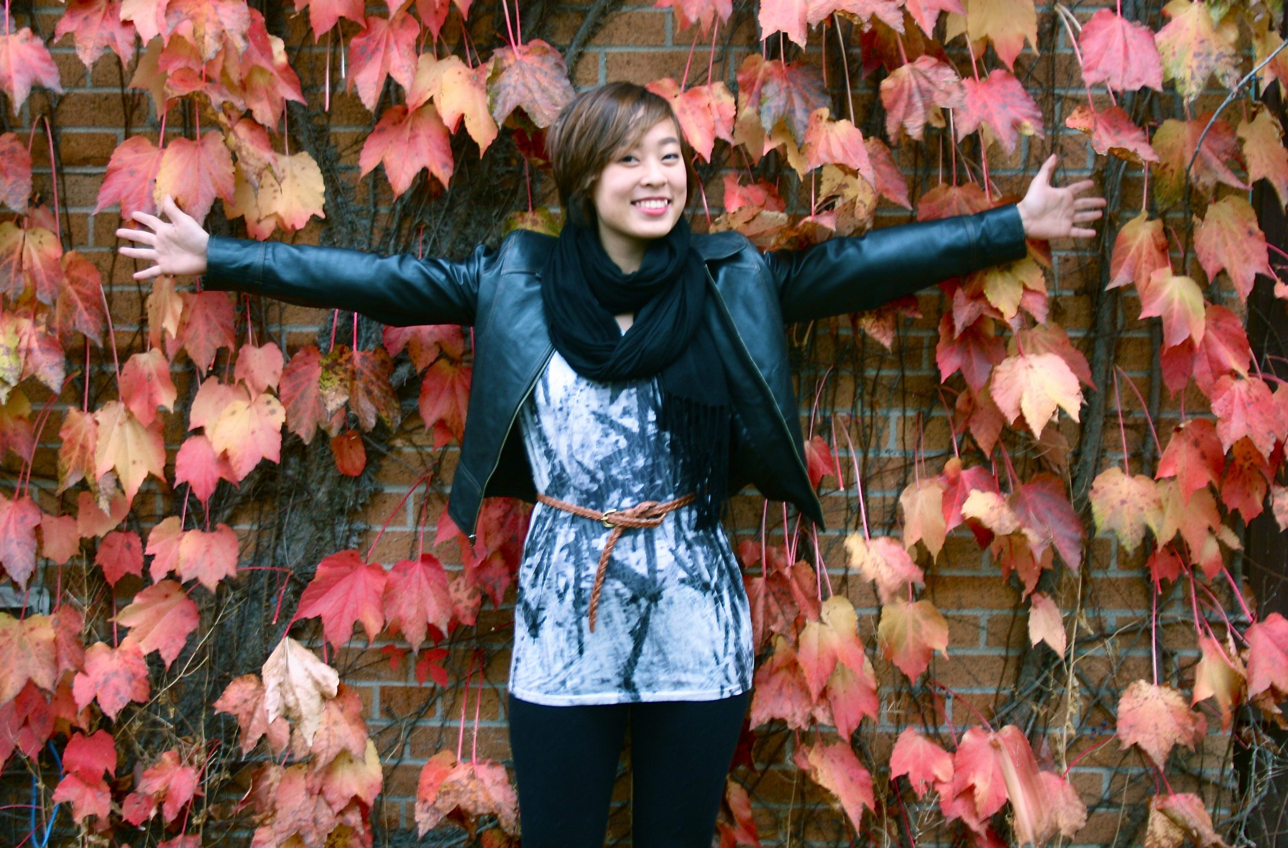 Ly Phuong Nguyen stands with arms outstretched in front of an ivy-covered wall on campus