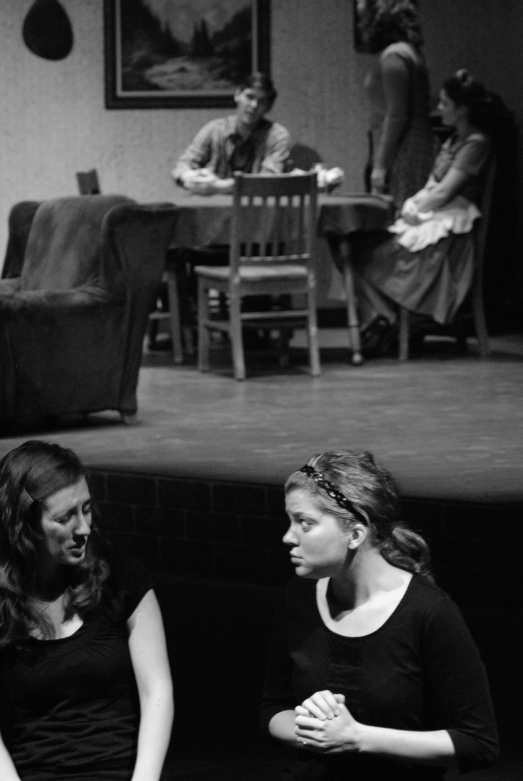 Black and white image of two ASL interpreters sitting on the edge of the Umble Center stage and interpreting the show taking place in the background
