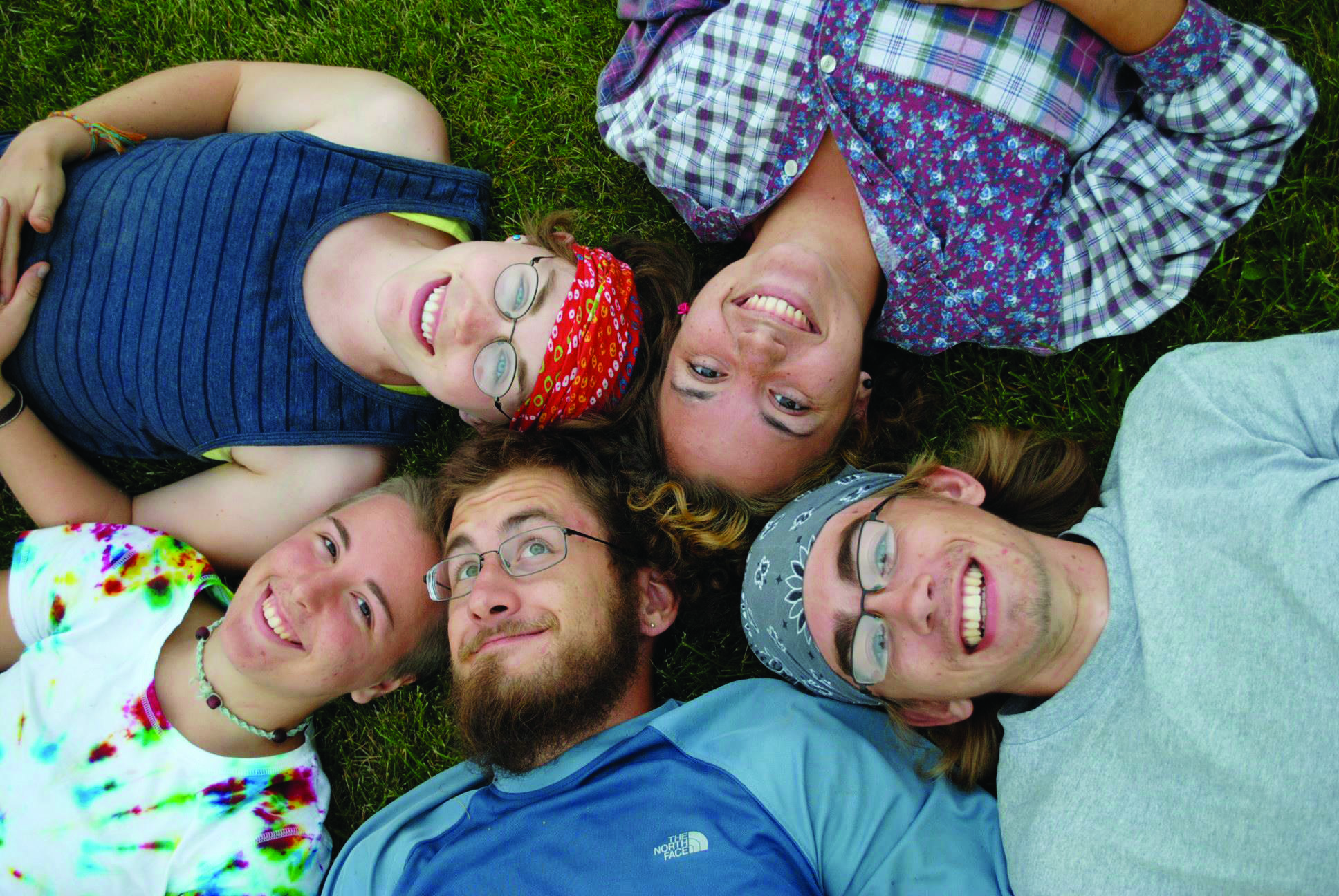 Students lay on grass heads together in Oregon