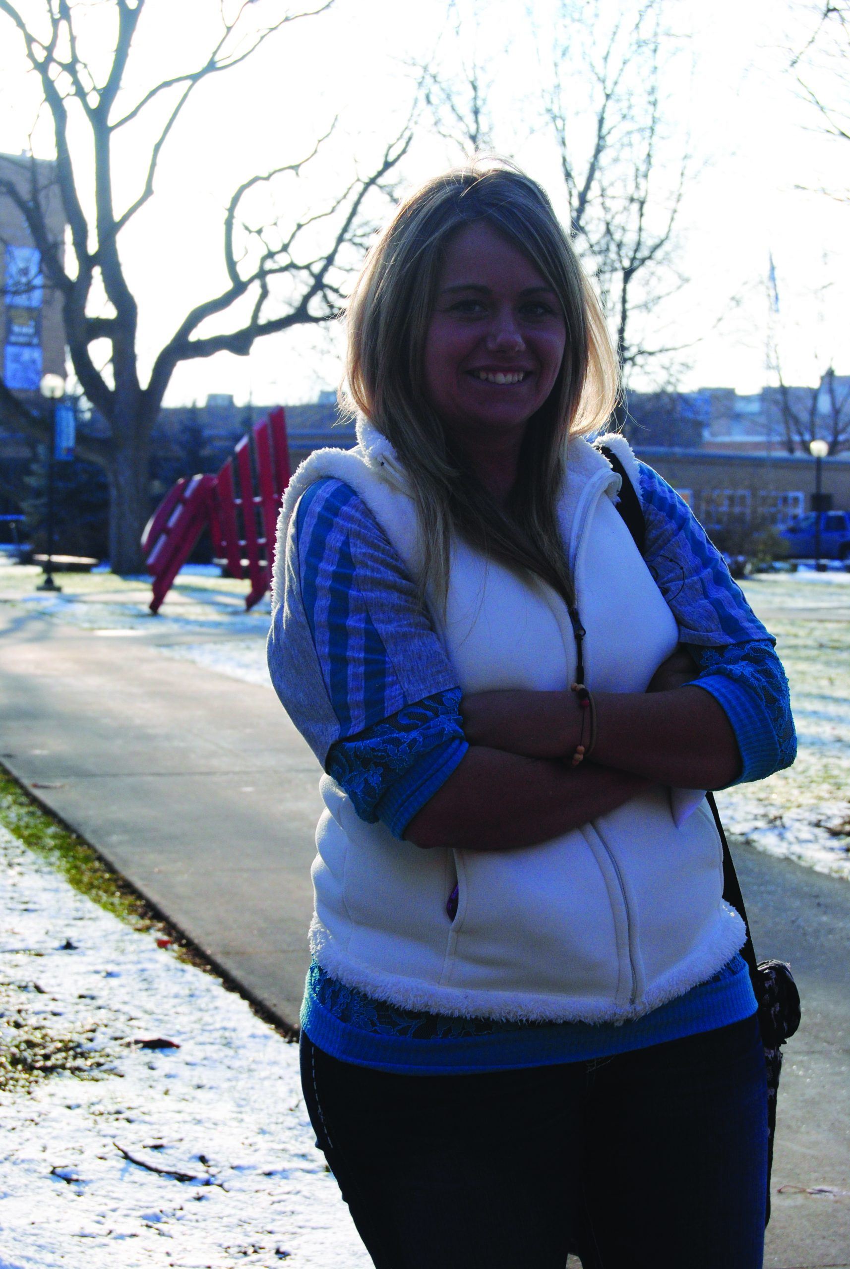 Naomi Kramer crosses her arms and smiles for the camera with the Goshen College campus as her backdrop
