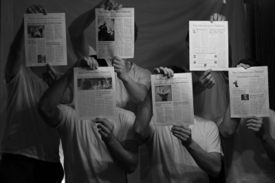 Black and white image of five students covering their faces with print editions of the Conscientious Objector newspaper