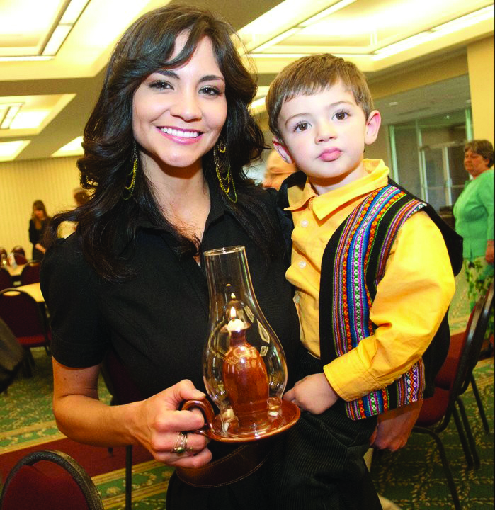 Daniela Zehr holds her son Micah and smiles for the camera in the Fellowship Hall