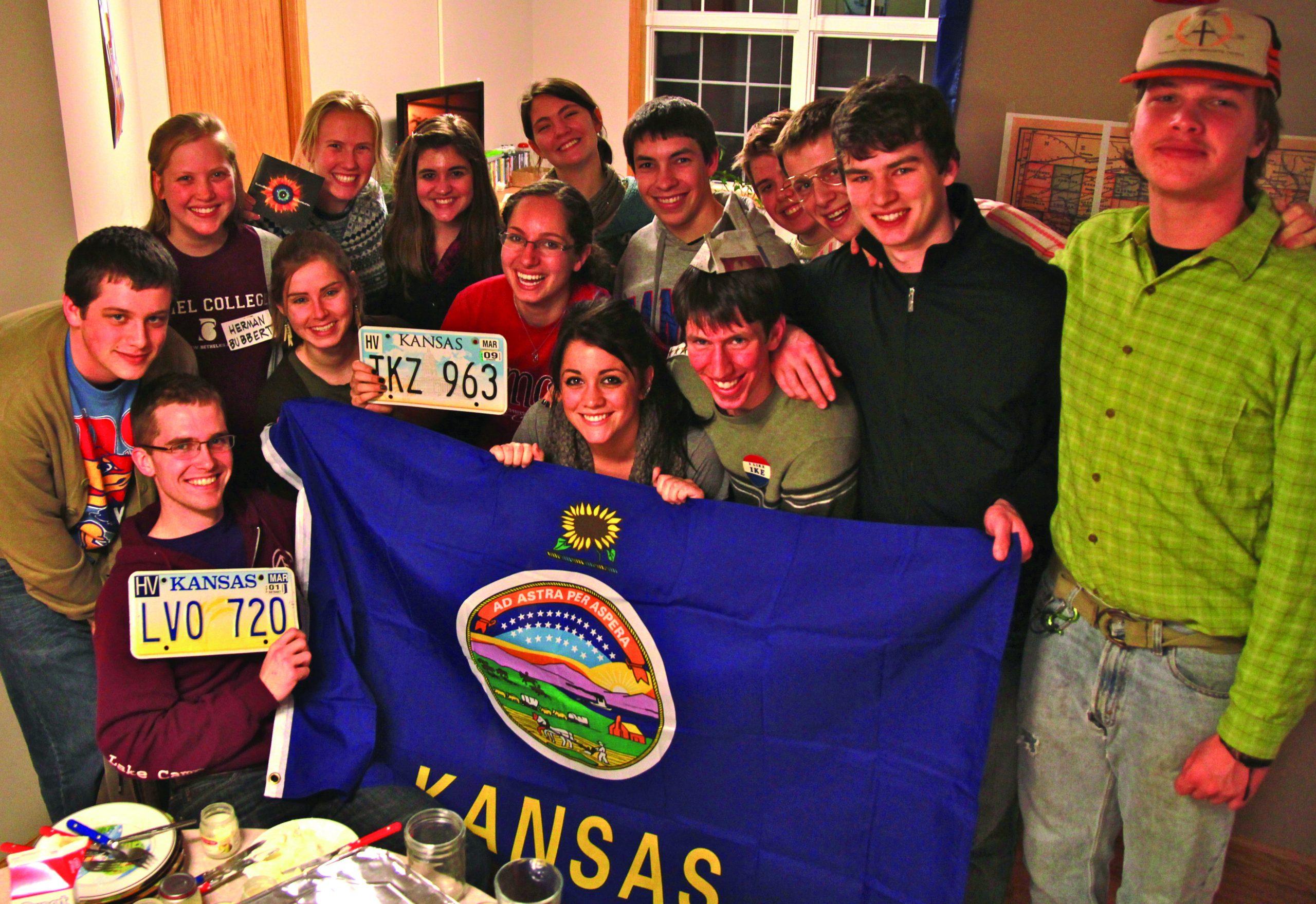 Members of Kansas Club hold up Kansas license plates and the Kansas flag