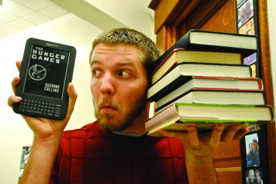 Lehman with a stack of books and an e-reader