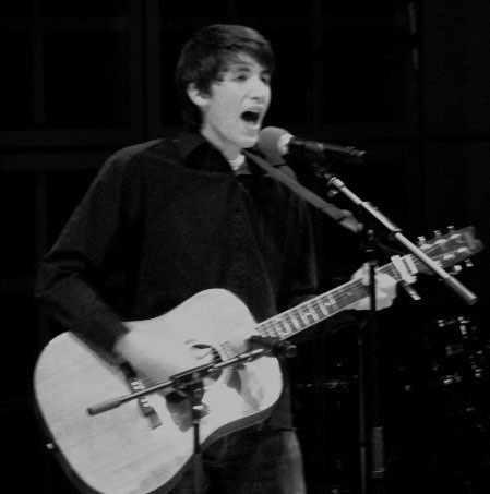Nathaniel Tann plays guitar and sings into a microphone