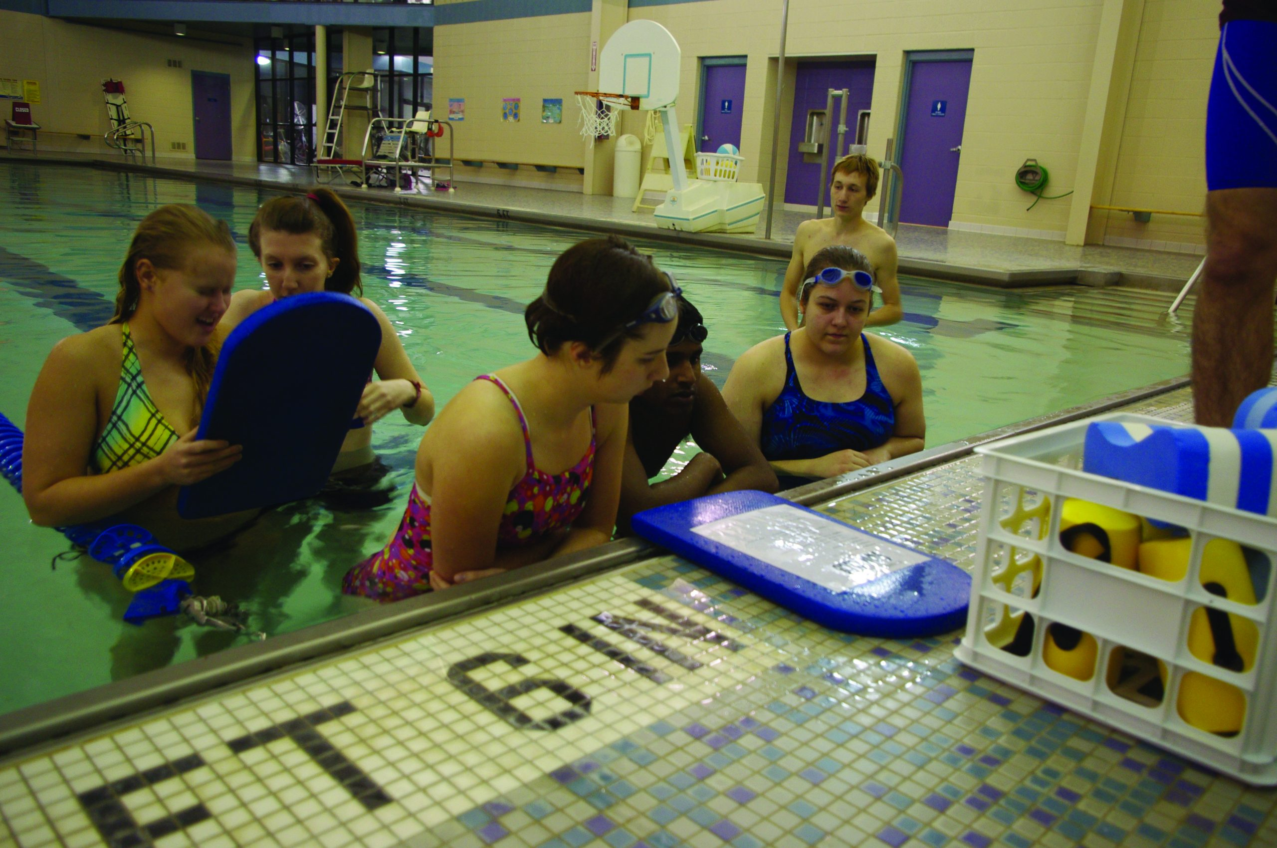 Six swimmers grab kickboards for a swim club workout in the RFC pool